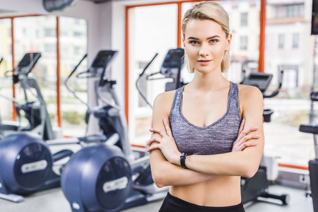 young attractive woman standing with crossed arms at gym in front of elliptical machines Imagens