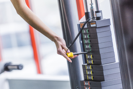 cropped shot of woman adding weight bars on gym machine Stock fotó
