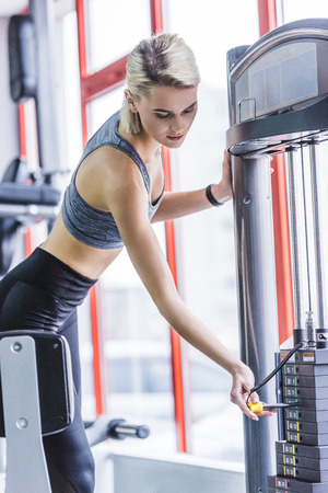 sportive young woman adding weight on gym machine Stock fotó