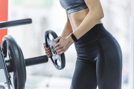 cropped shot of sportive woman adding weight plate to gym machine Stock fotó