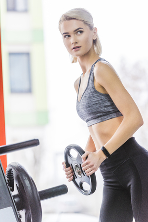 sportive young woman adding weight plate to gym machine Stock fotó - 114412359