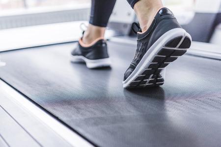 bijgesneden opname van een vrouw in jogging-sneakers die op een loopband loopt