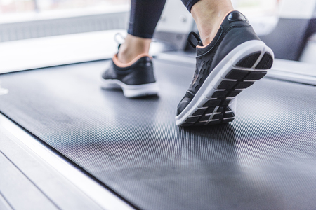 cropped shot of woman in jogging sneakers running on treadmill 版權商用圖片 - 114412396