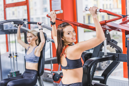 young sportive women working out with gym machines