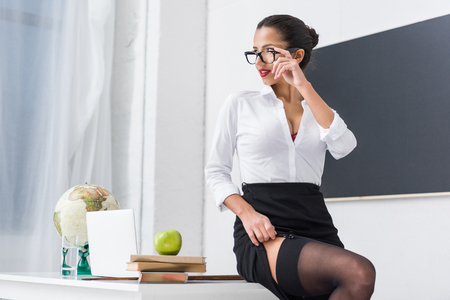 young teacher in stockings sitting on desk at classroom
