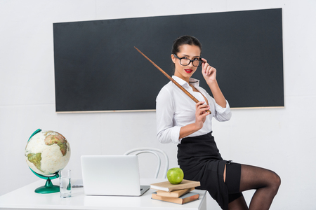 young sexy teacher in stockings with pointer sitting on desk in front of chalkboard Standard-Bild