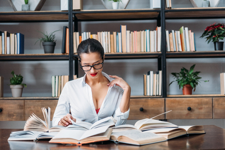 young teacher in unbuttoned shirt reading at library