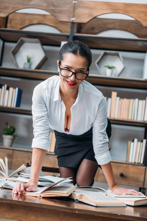 young teacher in unbuttoned shirt on table at library