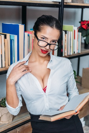 young sexy teacher readin book at library while leaning on bookshelves Stockfoto