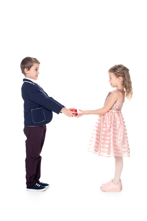 side view of stylish boy presenting heart shaped gift box to beautiful little girl isolated on white Stock Photo