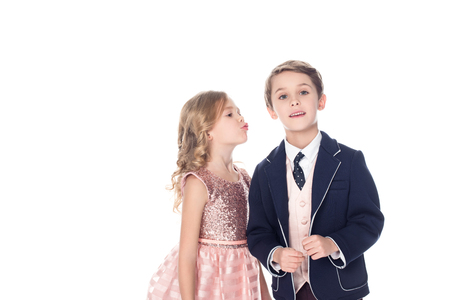 beautiful little girl able to kiss boy in suit looking at camera isolated on white Stock Photo