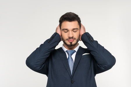 relaxed young businessman with closed eyes closing ears with hands isolated on grey