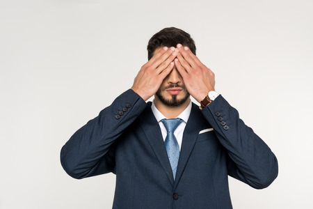 young businessman closing eyes with hands isolated on grey 스톡 콘텐츠