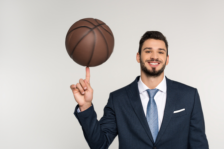 young businessman holding basketball ball on finger and smiling at camera isolated on grey Stok Fotoğraf