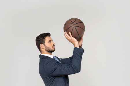 side view of young businessman throwing basketball ball isolated on grey 写真素材 - 114412489
