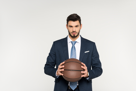 serious young businessman holding basketball ball and looking at camera isolated on grey