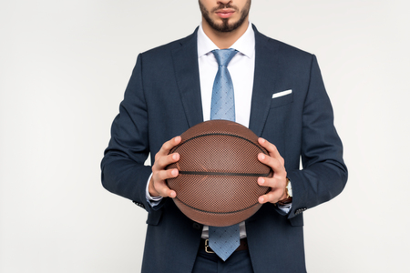 cropped shot of young businessman holding basketball ball isolated on grey