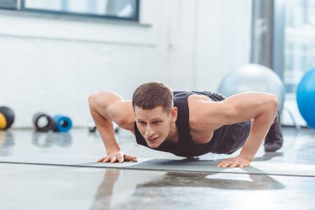 young sportsman doing push ups on yoga mat Stock Photo