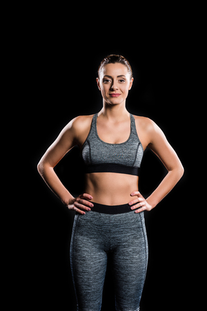 athletic young woman in sportswear looking at camera isolated on black Stock Photo