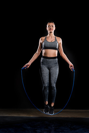 sportswoman jumping with skipping rope and looking at camera on black Stock fotó