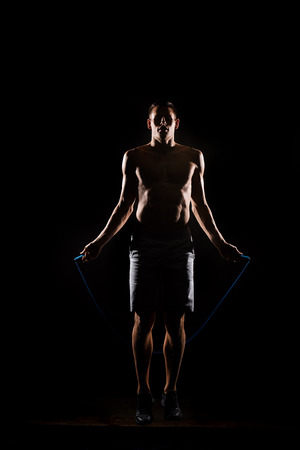 silhouette of sportsman jumping with skipping rope on black