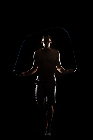 silhouette of athletic sportsman jumping with skipping rope isolated on black