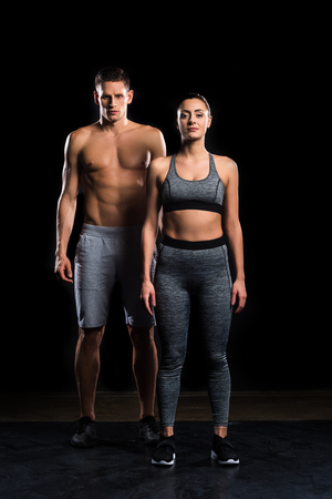 athletic young couple in sportswear looking at camera on black