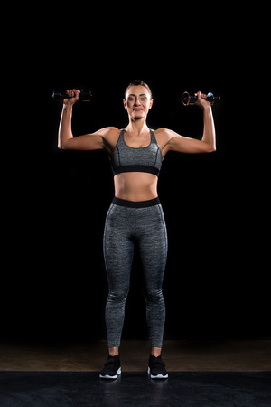 athletic sportswoman holding dumbbells and smiling at camera on black