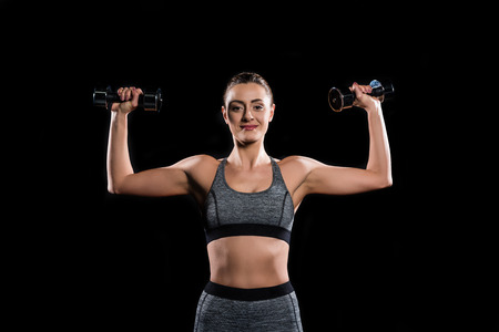 young sportswoman holding dumbbells and smiling at camera on black