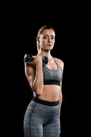 athletic sportswoman holding dumbbell and looking at camera isolated on black Imagens