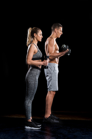 side view of sporty young couple exercising with dumbbells on black Foto de archivo