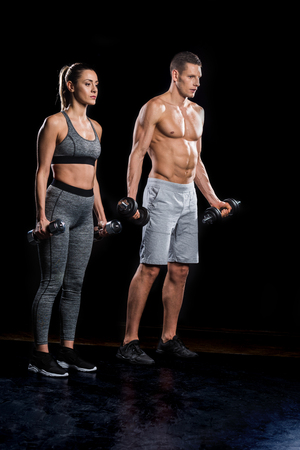 athletic young couple in sportswear exercising with dumbbells on black