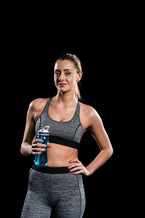young sportswoman holding bottle of water and looking at camera isolated on black