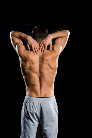 back view of muscular shirtless sportsman standing isolated on black Banco de Imagens