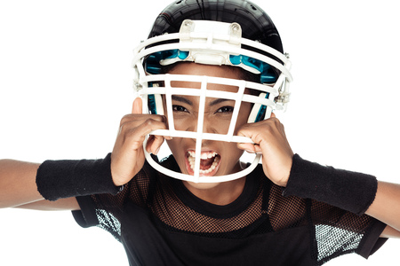 high angle view of agressive female american football player trying to take off her helmet isolated on white