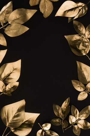 close up view of shiny golden leaves isolated on black Stockfoto