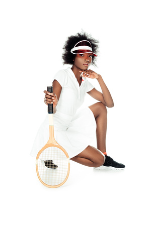 serious female tennis player with racket sitting on floor isolated on white