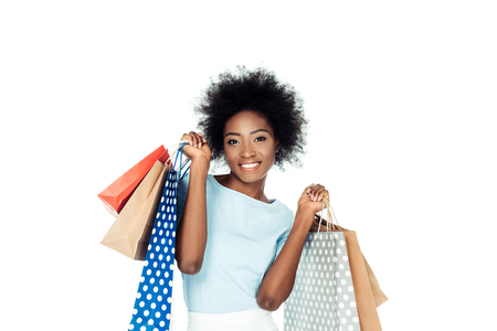 happy woman holding various shopping bags isolated on white