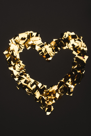 top view of golden confetti arranged in heart shape isolated on black Imagens