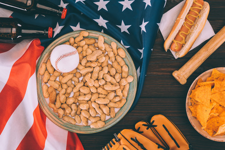 top view of baseball ball on plate with peanuts, baseball bat, glove, hot dog and beer bottles on american flag