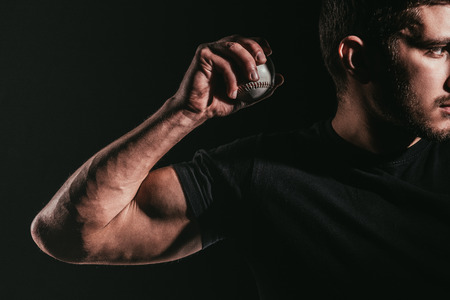cropped shot of young muscular sportsman holding baseball ball isolated on black Banco de Imagens