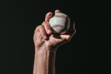 partial view of sportsman holding baseball ball isolated on black 免版税图像