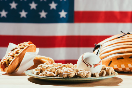 close-up view of baseball ball on plate with peanuts, leather glove and hot dogs on table with us flag behind Stock Photo