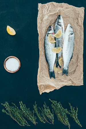 top view of healthy fish with lemon slices on paper on black