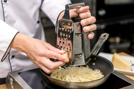 cropped image of chef grating cheese on grater Stock Photo