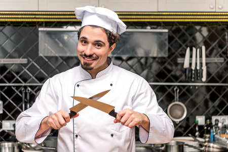 smiling chef standing with crossed knifes