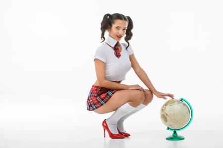 schoolgirl in red plaid skirt sitting with globe on white