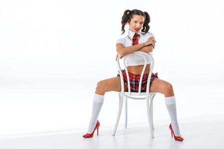 young seductive schoolgirl sitting on vintage chair isolated on white Foto de archivo