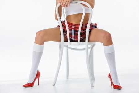 cropped shot of sexy schoolgirl sitting on chair isolated on white