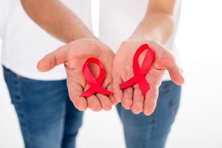 cropped shot of couple with aids ribbons in hands isolated on white Stock Photo